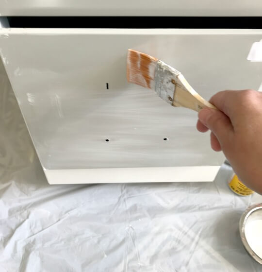 applying Mod Podge to the file cabinet